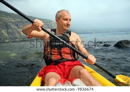 Mature man kayaking in the ocean on Big Island, Hawaii - stock photo