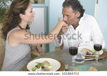 Mature man kissing woman's hand while having a healthy lunch at home. - stock photo