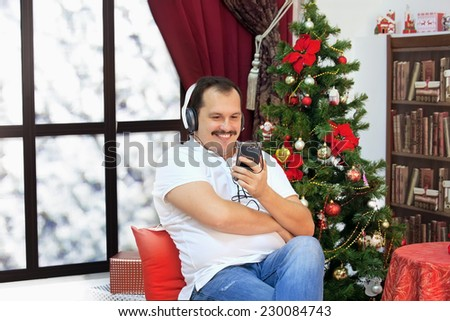 Mature man listening to music on headphones near a christmas tree - stock photo