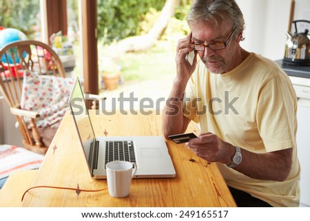 Mature Man Making On Line Purchase Using Credit Card - stock photo