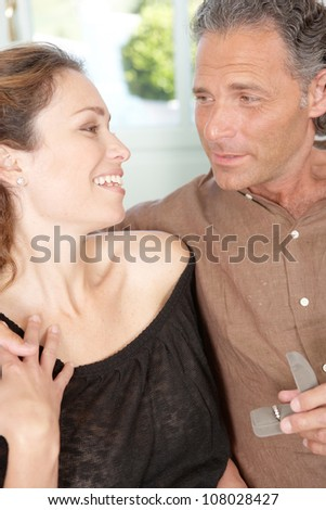 Mature man offering engagement ring to mature woman while sitting on a white sofa at home. - stock photo