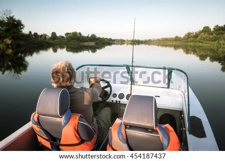 Mature man on a motor boat. Fishing. - stock photo