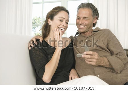 Mature man proposing marriage to a woman and offering her an engagement ring. - stock photo