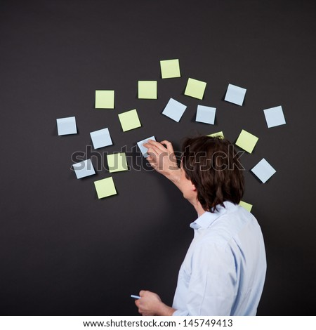 mature man putting notes on black wall - stock photo