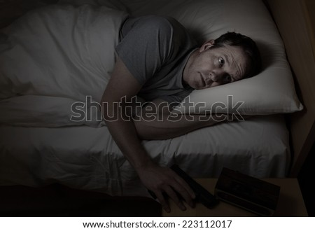 Mature man reaching for pistol in dark bedroom with scared look on his face  - stock photo