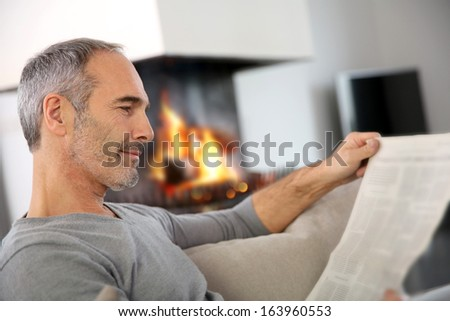 Mature man relaxing by fireplace with newspaper - stock photo