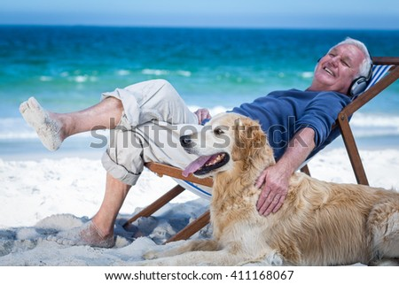 Mature man resting on a deck chair listening to music petting his dog on the beach - stock photo
