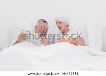 Mature man showing his newspaper to his wife in bed - stock photo
