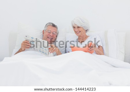 Mature man showing newspaper to his wife in bed - stock photo