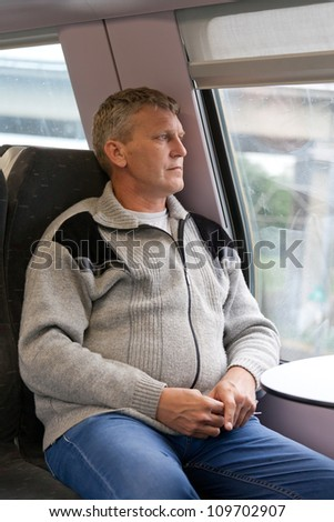 mature man sits in a car of a train and looks out of the window - stock photo