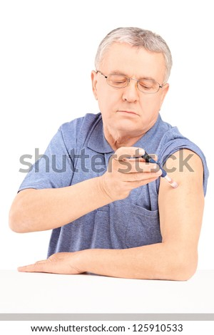 Mature man sitting and injecting insulin in his arm isolated on white background - stock photo