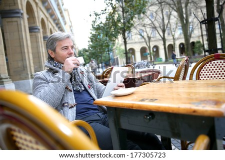 Mature man sitting at coffee shop table with tablet - stock photo
