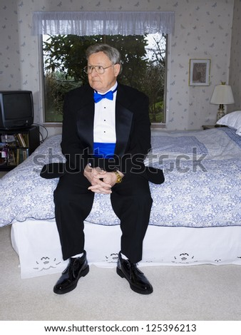 Mature man sitting on bed in tuxedo - stock photo