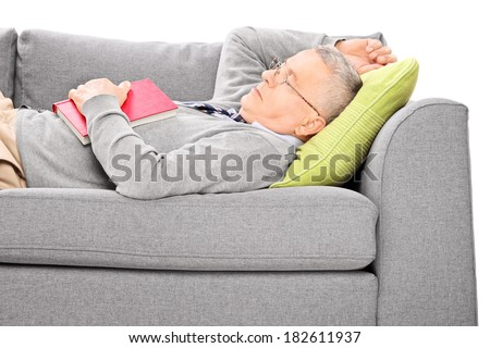Mature man sleeping on sofa and holding a book isolated on white background - stock photo