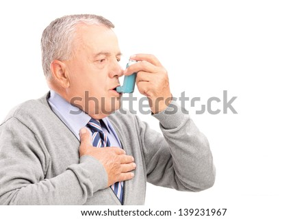 Mature man taking asthma treatment, isolated on white background - stock photo