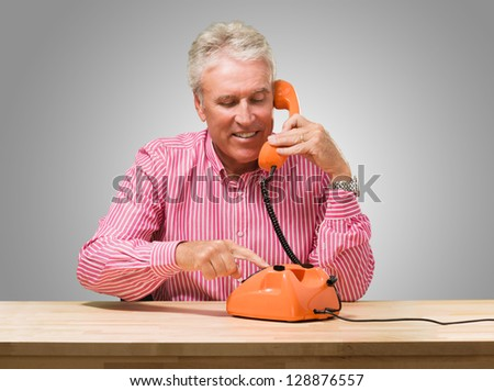 Mature Man Talking On Telephone against a grey background - stock photo