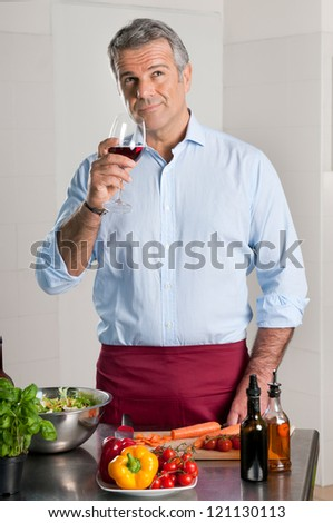 Mature man tasting a glass of red wine while cooking at home - stock photo