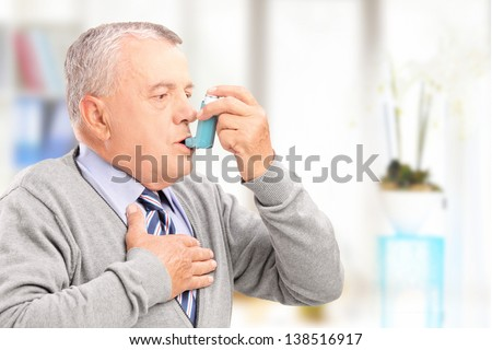 Mature man treating asthma with inhaler at home - stock photo
