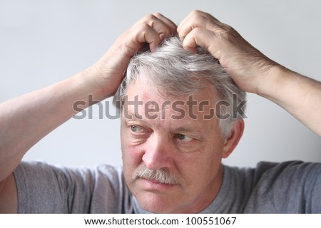 mature man uses both hands to scratch his head - stock photo