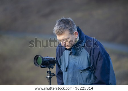 Mature Man using Camcorder outdoors - stock photo