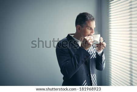 Mature man with cup of coffee - stock photo