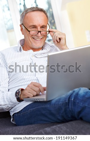 Mature man with laptop and reading specs - stock photo