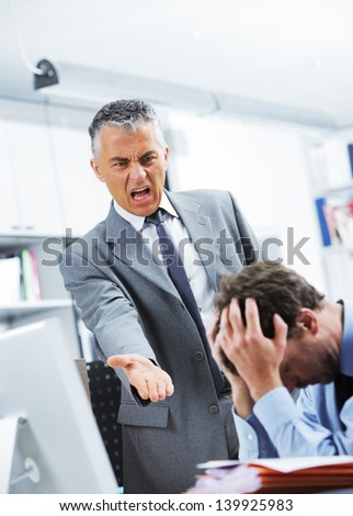Mature manager shouting at his office worker - stock photo