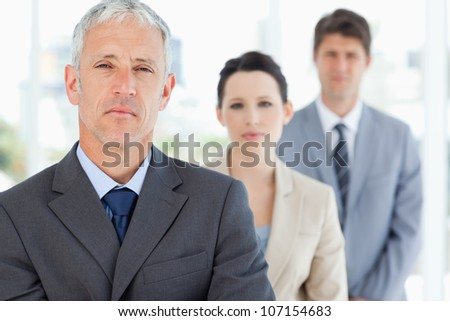 Mature manager standing upright in front of his serious team - stock photo