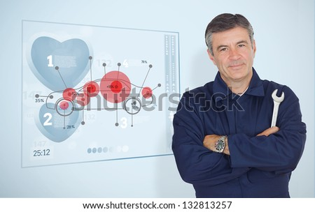 Mature mechanic standing next to futuristic interface with diagram - stock photo