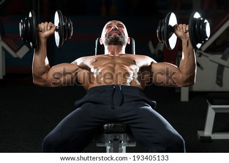 Mature Men Doing Dumbbell Incline Bench Press Workout In Gym - stock photo