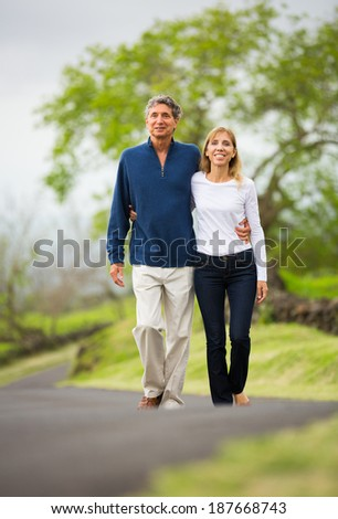 Mature middle age couple in love walking in countryside - stock photo