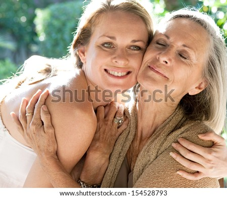 Mature mother and adult daughter spending time together in a home garden hugging tightly and affectionately cuddling during a bright and golden summer sunny day outdoors. - stock photo