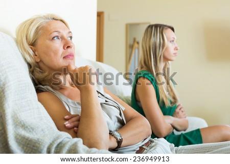 Mature mother and sad adult daughter having quarrel - stock photo