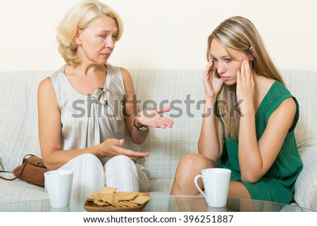 Mature mother with  adult daughter having serious conversation on sofa at home - stock photo
