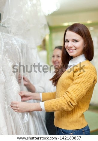 Mature mother  with daughter chooses white gown at shop of wedding fashion - stock photo
