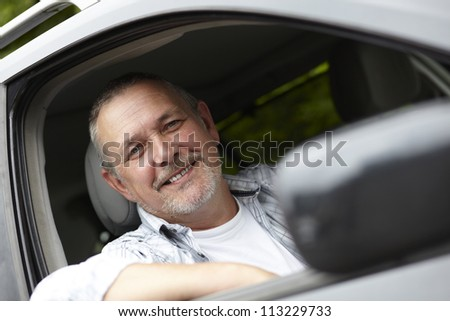 Mature Motorist Looking Out Of Car Window - stock photo