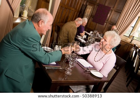 Mature older couples enjoying a celebration in a restaurant - stock photo