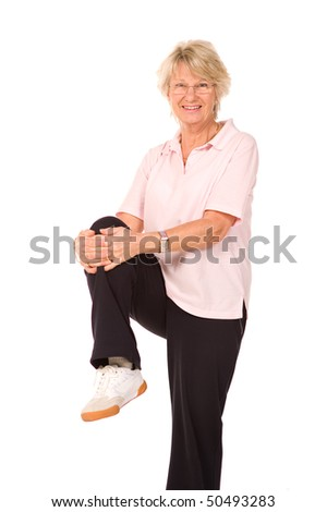 Mature older lady performing stretching exercises before gym workout - stock photo