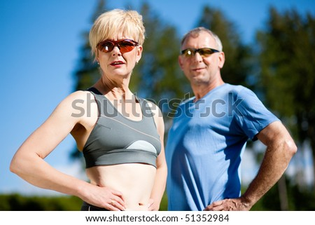 Mature or senior couple in jogging gear doing sport and physical exercise outdoors - stock photo
