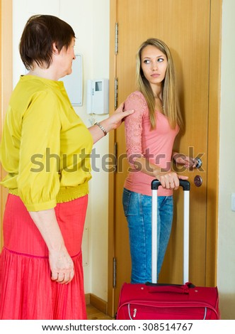 Mature owner of apartment turning female lodger out  near door - stock photo
