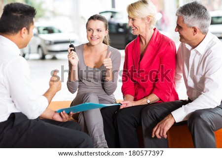mature parents buying a new car for their young adult daughter - stock photo