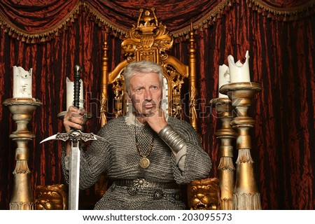 Mature pensive medieval knight on the throne - stock photo