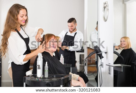 Mature person haircut at the hair salon with hairstylist and smiling - stock photo