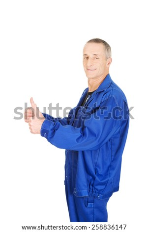 Mature repairman showing thumbs up. - stock photo