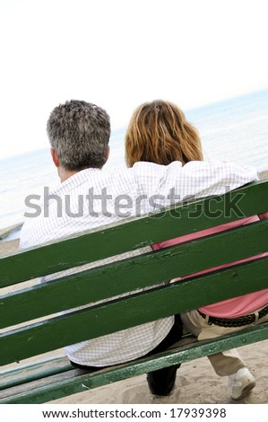 Mature romantic couple on a bench on seashore - stock photo