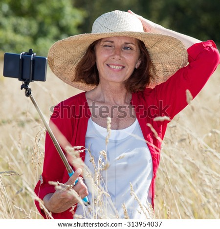 mature selfie concept - cheerful mature woman posing for selfie with a stick in summer dry meadows wearing a rural summer hat,natural daylight - stock photo