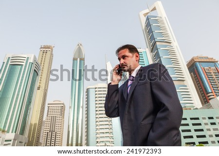 Mature serious businessman on the phone in the front of Dubai skyscrapers.Low angle view, copy space - stock photo