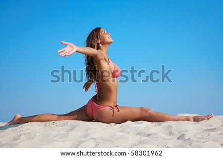 Mature sexy woman practicing gym by the beach - stock photo
