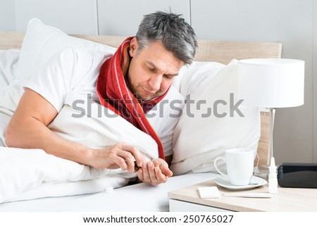 Mature Sick Man Lying On Bed Having Medicine - stock photo