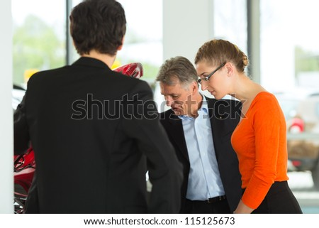 Mature single man with autos in light car dealership with a young couple, man and woman, looking beneath the hood he obviously is buying a car or is a car dealer - stock photo